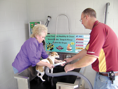 Scott Radford helps Debra Emory-Champlain give her dog, Jo-Jo, a bath Monday at the pet wash, a new portion of Radford's Car Wash facility on Highway 32-72 East.